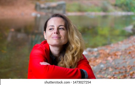 Pretty young hiking woman enjoying autumn on the bank of a beautiful wild river