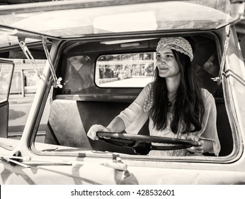 Pretty young hippie woman driving her vintage oldtimer car (black and white toned image, retro style)