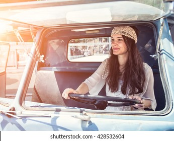 Pretty young hippie woman driving her vintage oldtimer car (color toned image, retro style)