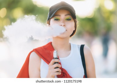 Pretty young hipster asian woman in black hat vape ecig, vaping device at the sunset. Toned image. Closeup.