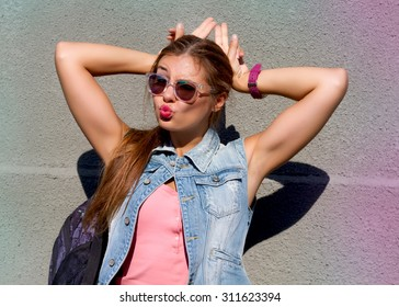 Pretty young hipster girl doing emotion,hands raised up in the form of rabbit ears with long hair dressed in blue jeans vest and trendy sunglasses going crazy outdoor and sending kisses at grey wall