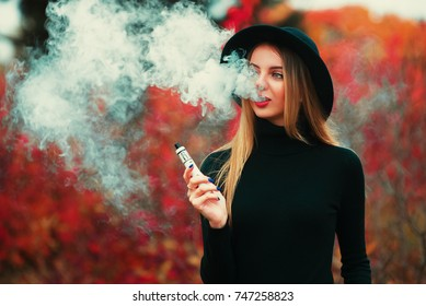 Pretty young hipster woman in black hat vape ecig, vaping device.
