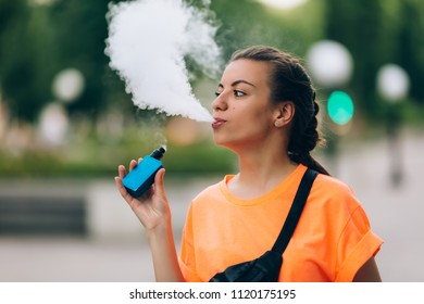 Pretty young hipster woman vape ecig, vaping device at the sunset. Toned image.