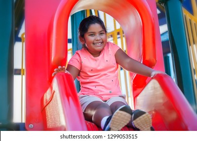 A pretty young hispanic girl with a cute smile looks relaxed as she prepares to slide down a playground slide.