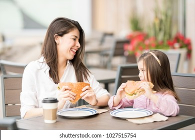 Pretty young hispanic mother and daughter eating a big burger at a cafe and smiling