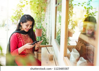 Pretty young indian woman using phone in a cafe