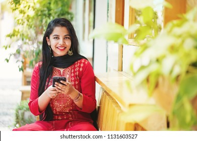 Pretty young indian woman using her phone and looking at camera