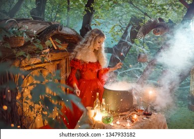 pretty young lady with blond curly hair above big magic cauldron with smoke and bottles with liquids, forest nymph in long bright red dress with loose sleeves prepares potion near wooden house