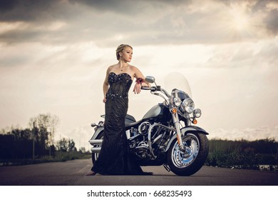 Pretty young lady in a classic black gown and motorcycle at sunset on highway