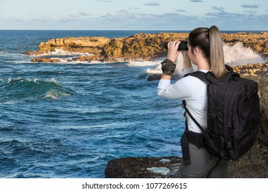 Pretty Young Lady Hiker with Binoculars and Backpack at the Coast
