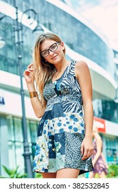 Pretty young lady in a light summer dress. Beautiful girl in glasses.