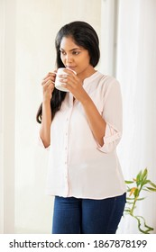 Pretty young lady relaxing with coffee cup at living room.