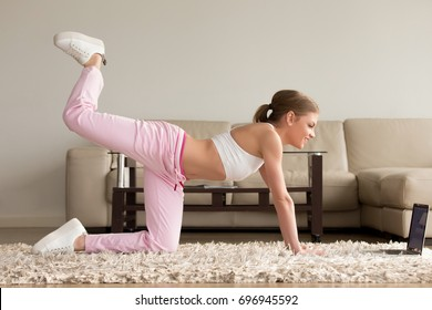 Pretty young lady in sportswear doing one knee kickbacks and watching aerobics videos on laptop, repeating exercise with online personal fitness trainer while training on carpet in living room at home