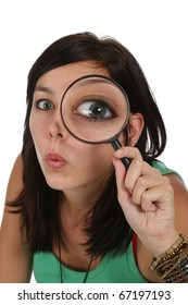 Pretty young lady with surprised  expression looking through a magnifying glass
