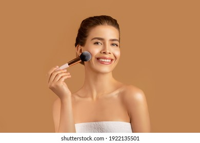 Pretty young lady using cosmetic brush to apply decorative makeup on her face, brown studio background. Millennial woman putting on blusher, looking at camera and smiling