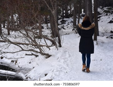 Pretty young lady walking along Upper Grassi Lake in the Canadian Rockies (Canmore, Alberta)