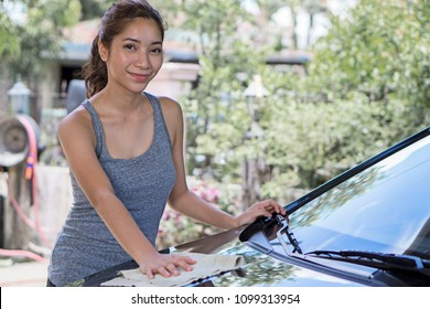 Pretty young lady washing her car.