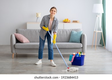 Pretty young lady wiping floor with mop, doing house cleanup, free space. Positive housewife tidying her apartment, doing household chores. Professional sanitary service concept