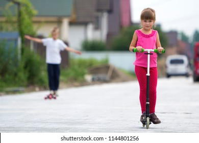 pretty young long-haired blond child girl in pink clothing with scooter on  sunny suburb