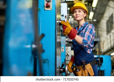 Pretty young machine operator wearing checked shirt and overall carrying out start-up works, interior of manufacturing plant on background