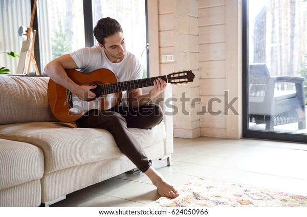明るいリビングルームでソファーに座りながらギターを弾く美しい若い男性