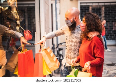 Pretty young man pointing to shop window to show clothing item his likes to his girlfriend - Beautiful young couple enjoying in shopping, having fun together, with the face mask -