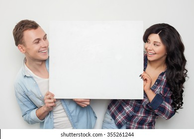 Pretty young man and woman are holding a white empty billboard together. They are looking at each other with joy. The friends are standing and smiling