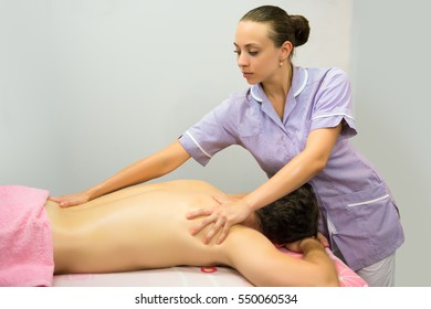 Pretty young masseuse giving back therapy to a male client
