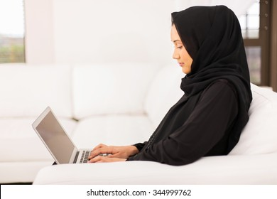 pretty young middle eastern woman using laptop at home