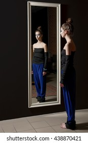 Pretty young model in fashion trousers and wool top near wall mirror