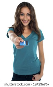 Pretty young model offering you a credit card. All on white background.