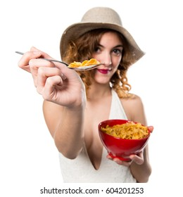 Pretty young model woman in swimsuit eating cereals from a bowl