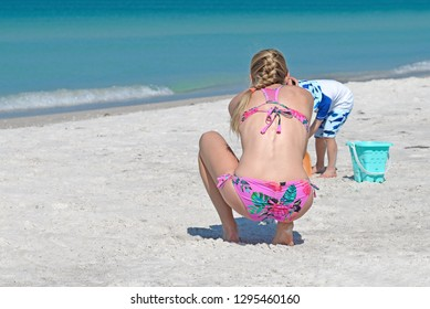 Pretty Young Mom in a Bikini Taking Photos of her Young Child Playing on the Beach