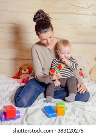 Pretty Young Mom with her Adorable Baby Boy Playing with Plastic Toys, Smiling at the Camera