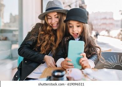 Pretty young mother and her cute daughter having fun and  take selfies. Little girl surprised looking in phone and smile on the sunny city background. Stylish family, true emotion, good moon.