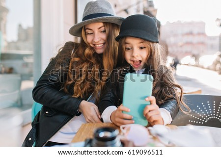 9bd896a3db0 Pretty young mother and her cute daughter having fun and take selfies. Little  girl surprised