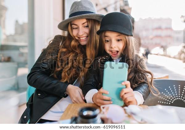 Mooie jonge moeder en haar schattige dochter plezier hebben en selfies nemen. Meisje verrast kijken in de telefoon en glimlach op de zonnige stad achtergrond. Stijlvolle familie, ware emotie, goede maan.