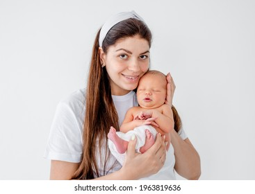 Pretty young mother holding in her hands adorable newborn baby, looking at the camera and smiling. Beautiful portrait of mom anf infant child at home. Girl with her little kid isolated on white