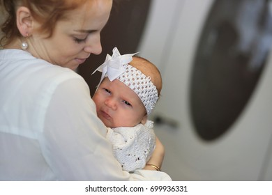 pretty young mother holding a newborn daughter in her arms