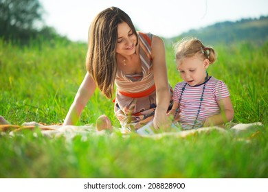 Pretty young mother reading book to her little daughter at green meadow
