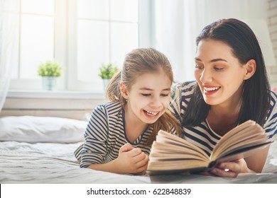 Pretty young mother reading a book to her daughter. Family holiday and togetherness.