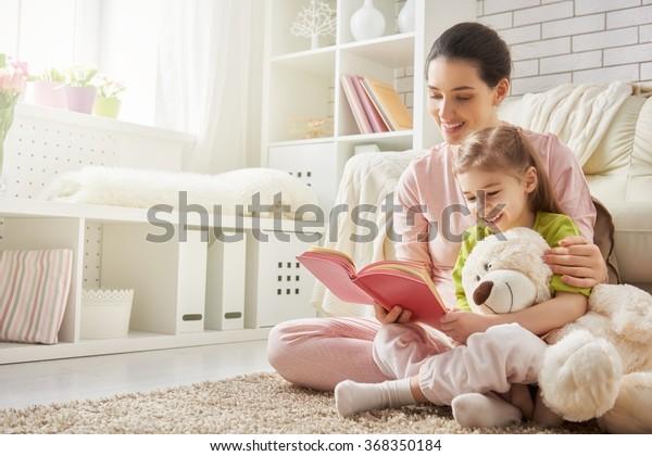 belle jeune mère lisant un livre à sa fille
