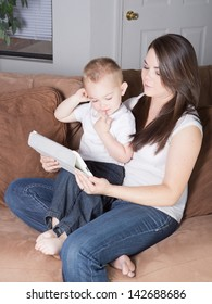 Pretty young mother reading with her son on a mobile wireless tablet computer device at home in the living room.