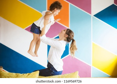 Pretty young mother in white shirt happily lifting little cute daughter up spending time together at home with colorful wall on background. Family values
