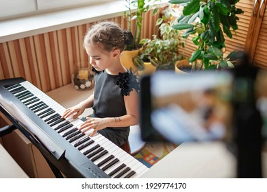 Pretty young musician in classic black dress playing digital piano at home during online concert and recording video, social distance during quarantine, online education concept, video blogging