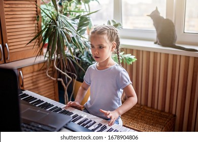 Pretty young musician playing classic digital piano at home during online class at home, social distance during quarantine, self-isolation, online education concept
