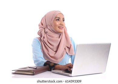A pretty young muslim lady is busy working and get idea at her desk isolated on white background