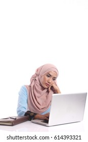 A pretty young muslim lady is busy working at her desk isolated on white background