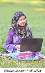 Pretty young muslimah student with notebook in action.