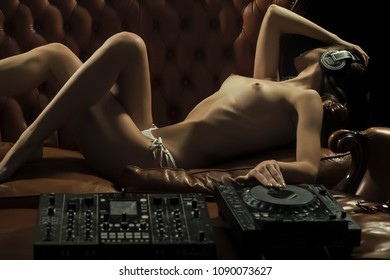 Pretty young naked dj woman in white panties and headphones with bare chest and nipples lying at table with mixer console on brown leather royal sofa in night club, horizontal picture